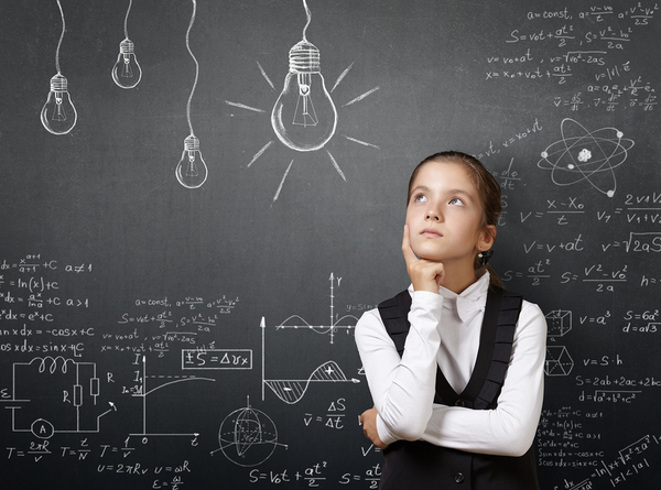 Female student in front of chalkboard appearing in deep thought.