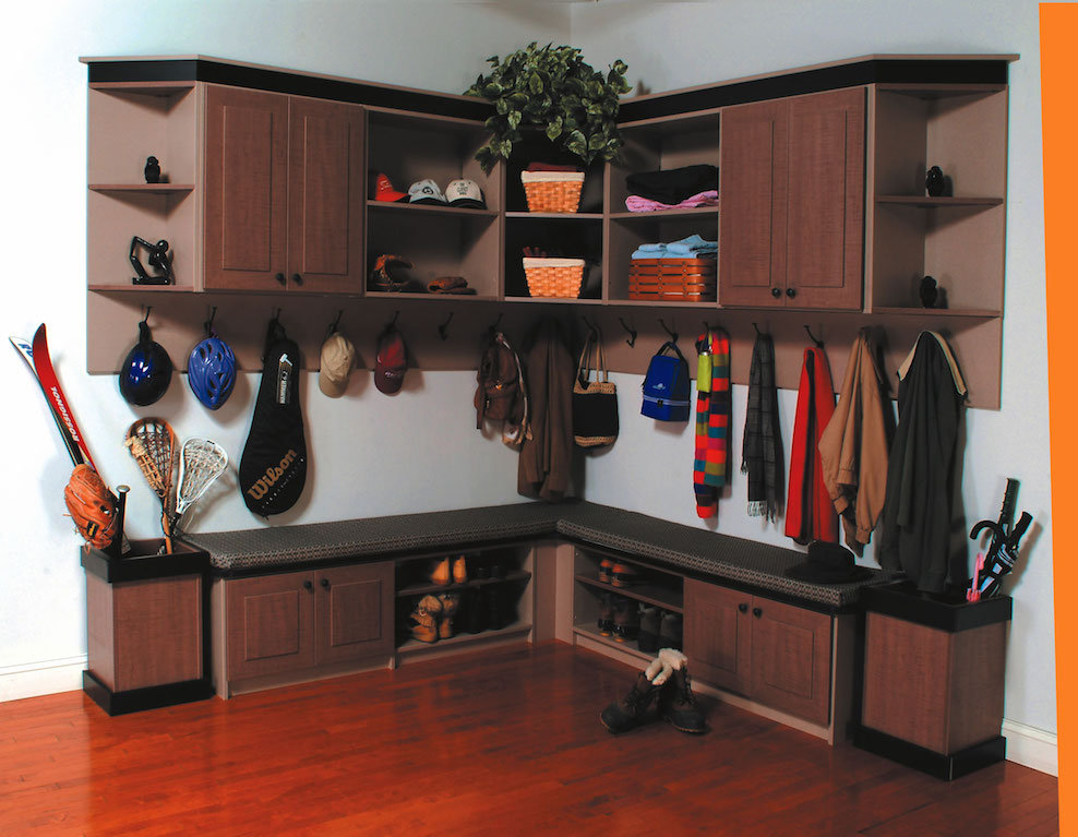 Entryway design with sports equipment hung on hooks and sitting benches with shoe storage underneath