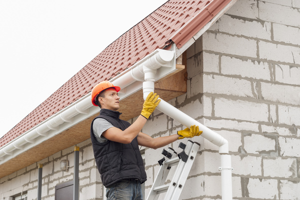 Installing gutters on a home.