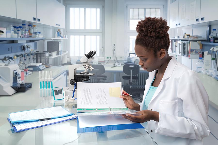 Lab scientist reading documents.