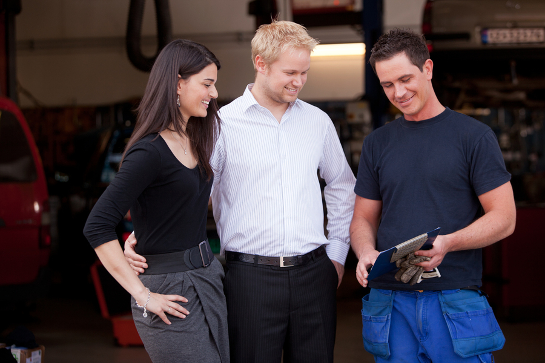 Happy customers speaking with a mechanic.