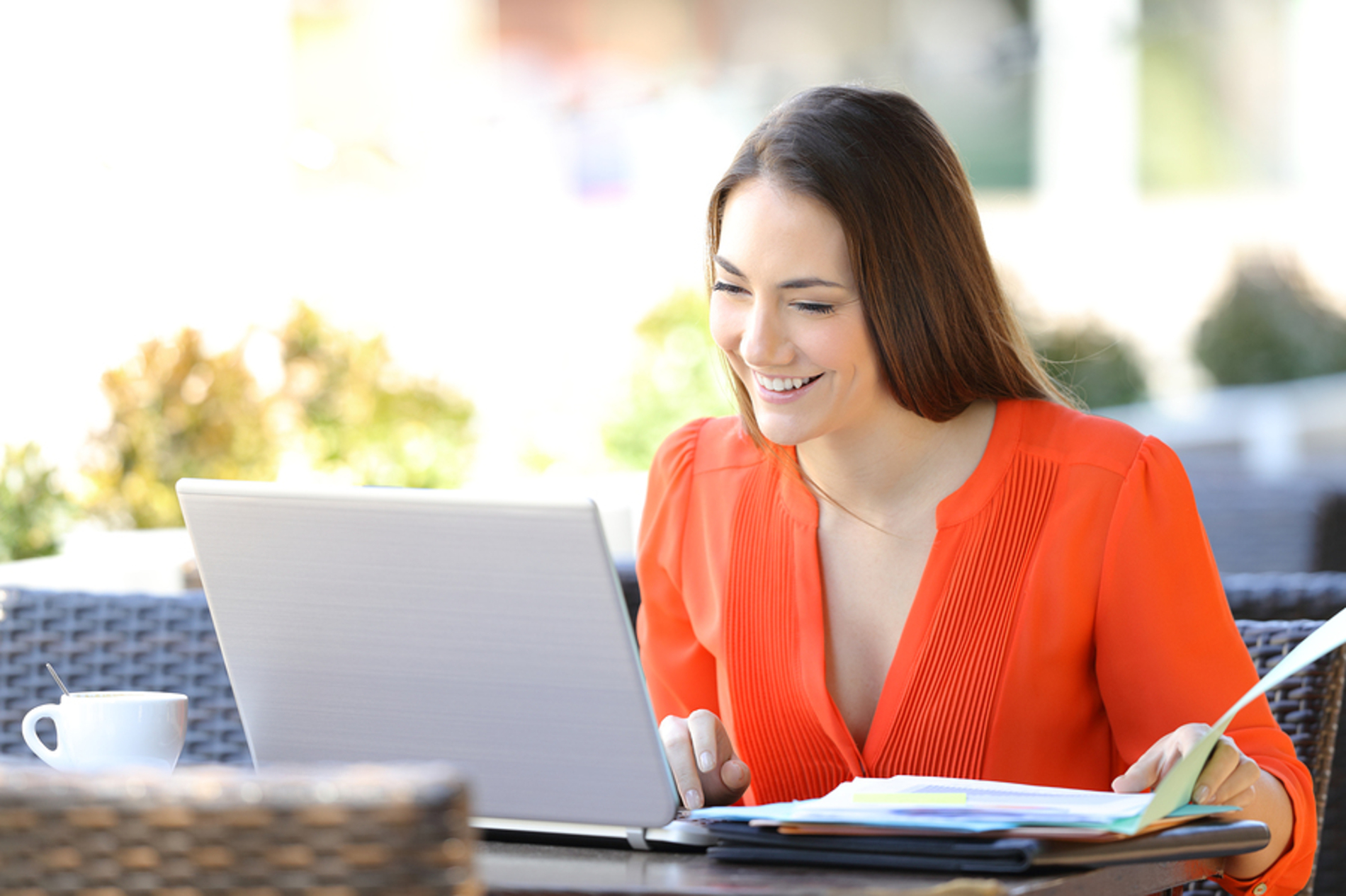 Woman smiling while looking at documents and her laptop screen.