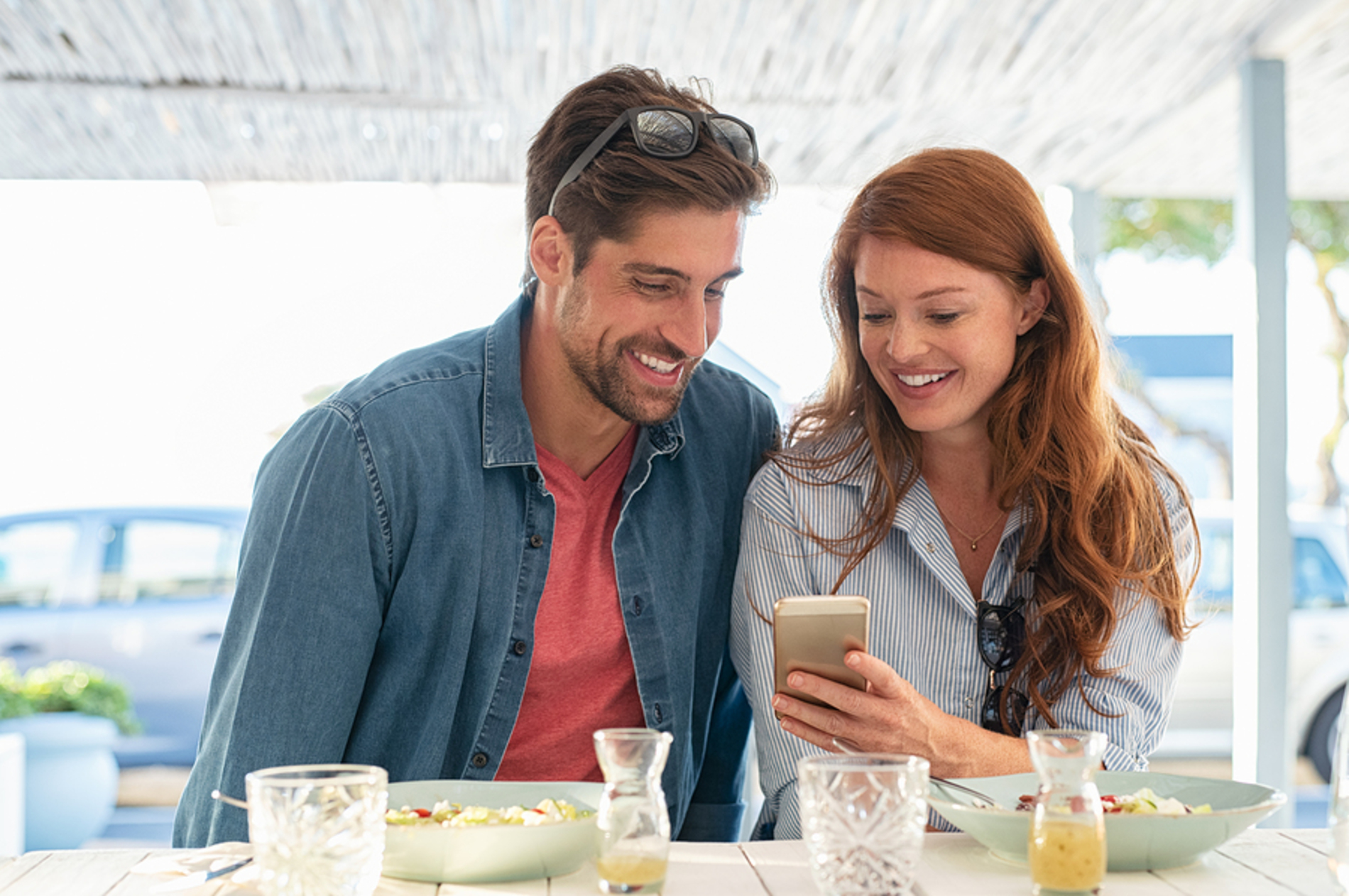 Couple sitting outside looking at a phone together while eating.