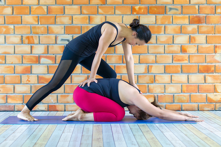 Woman getting assistance from a trainer while stretching.