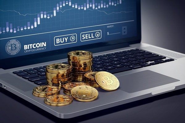 Gold bitcoin coins on top of a laptop.
