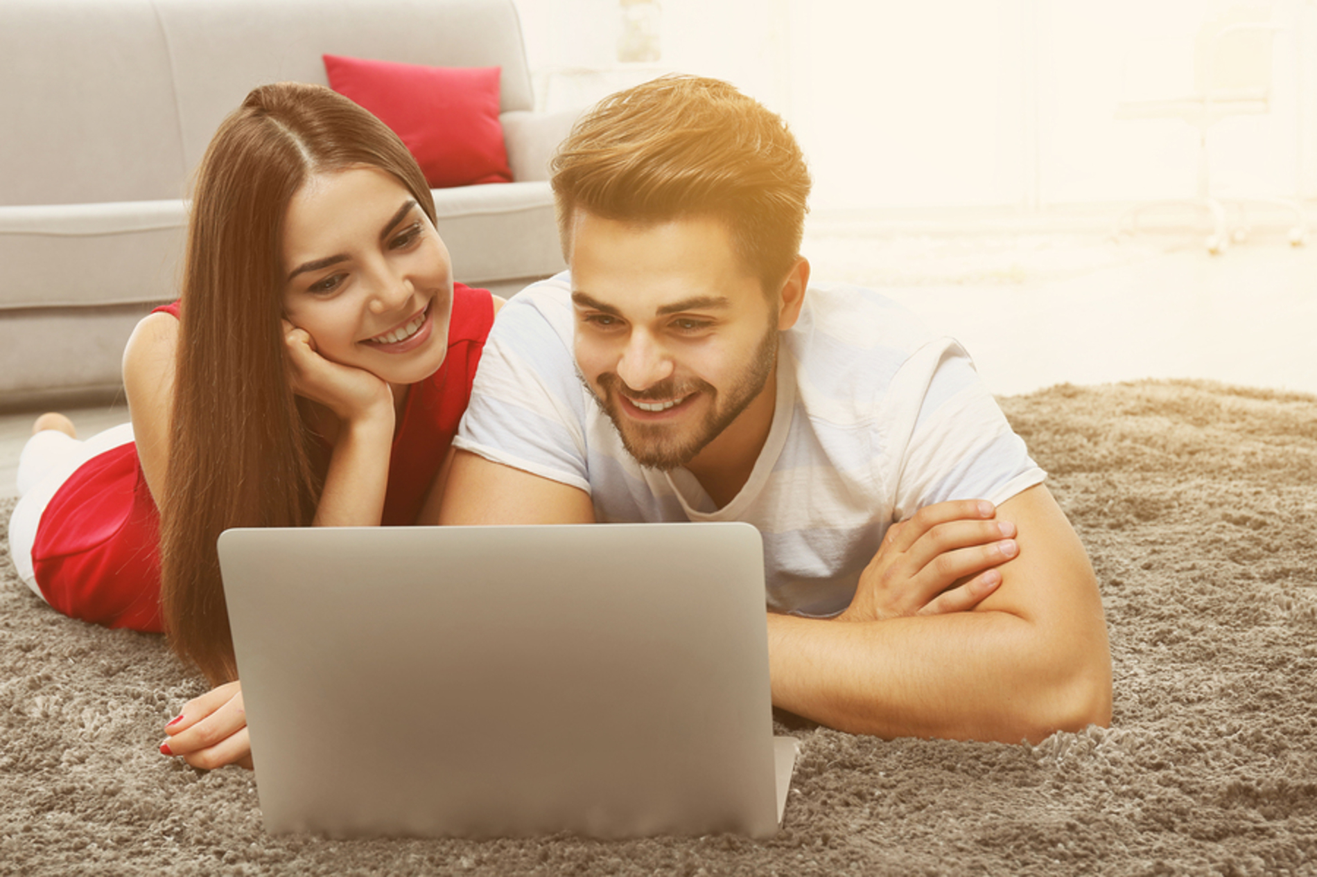 Couple lying on the floor looking at a laptop together.