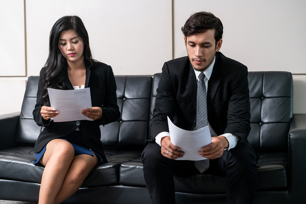 Two job candidates sitting on a couch holding resumes.