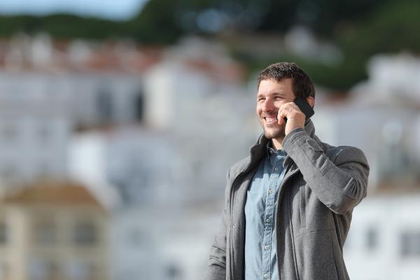 Smiling man speaking on a phone.