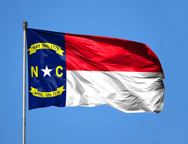 North Carolina flag flying with a blue sky in the background.