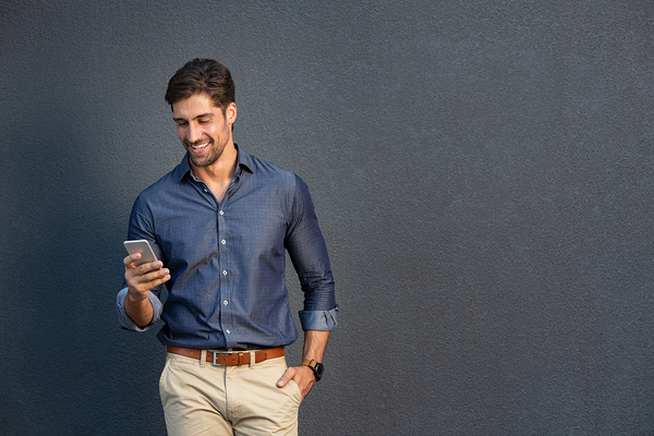 Man standing and looking at his phone.