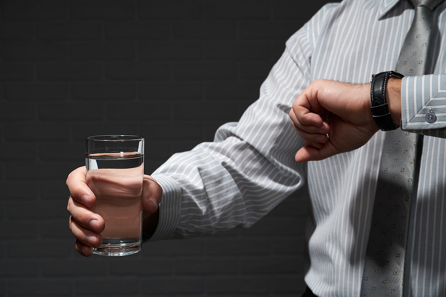 Man drinking a large glass of water.