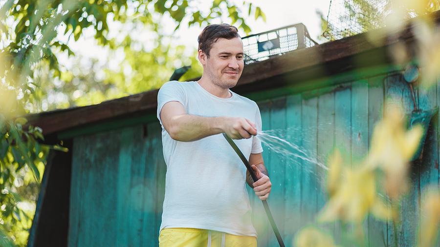 Man using a hose to water a garden.