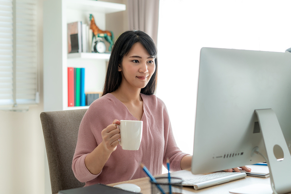 Woman looking at her desktop monitor while drinking a cup of coffee.