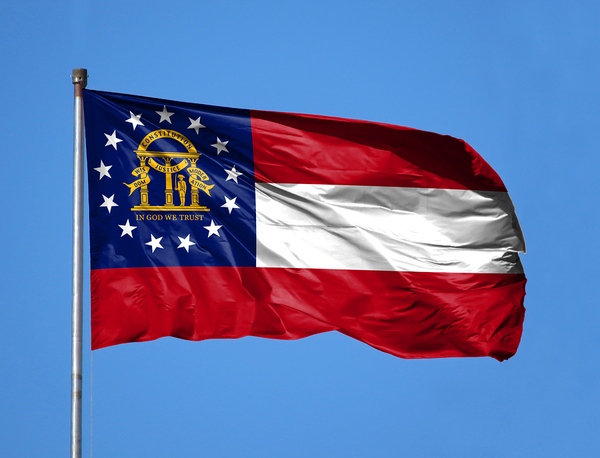 Georgia state flag flying with blue sky in the background.