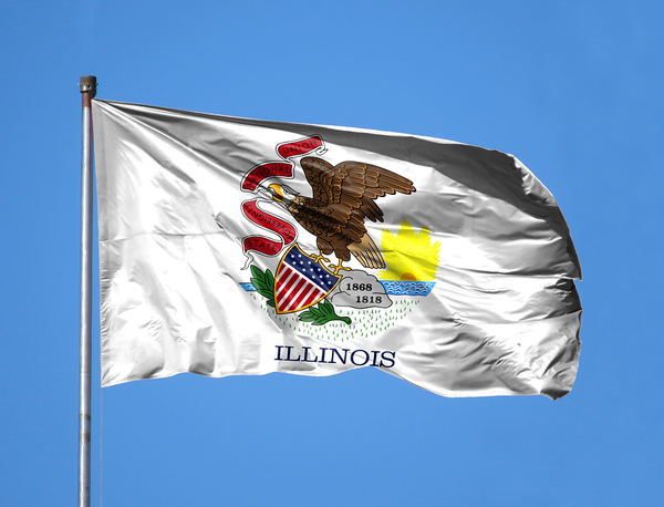 Illinois flag flying with a blue sky in the background.