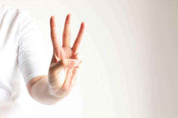 Person holding up three fingers.