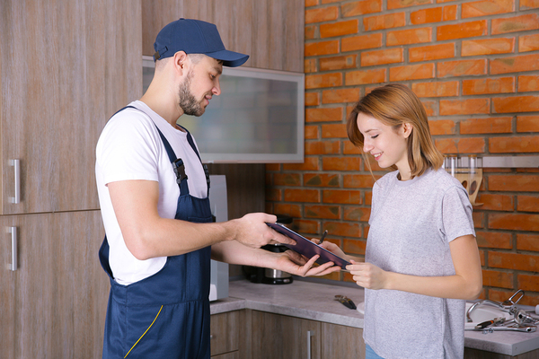 Home improvement contractor getting the signature of a woman on a tablet