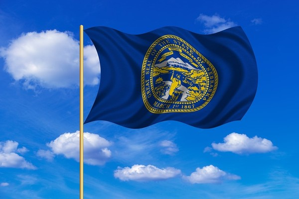 Nebraska state flag with blue sky and clouds in the background