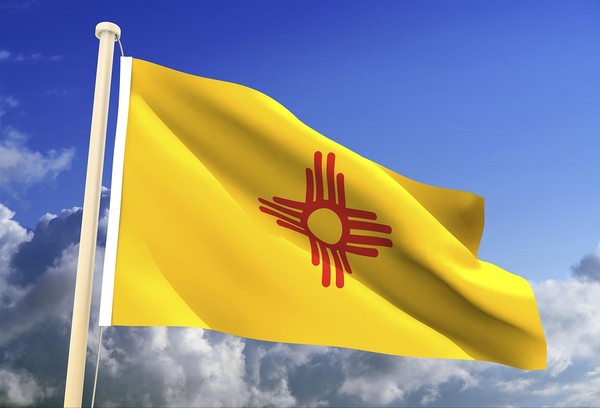 New Mexico flag flying with a blue sky in the background