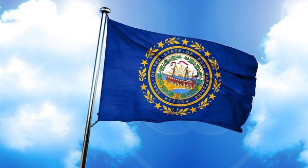 New Hampshire flag flying with blue sky and white clouds in the background