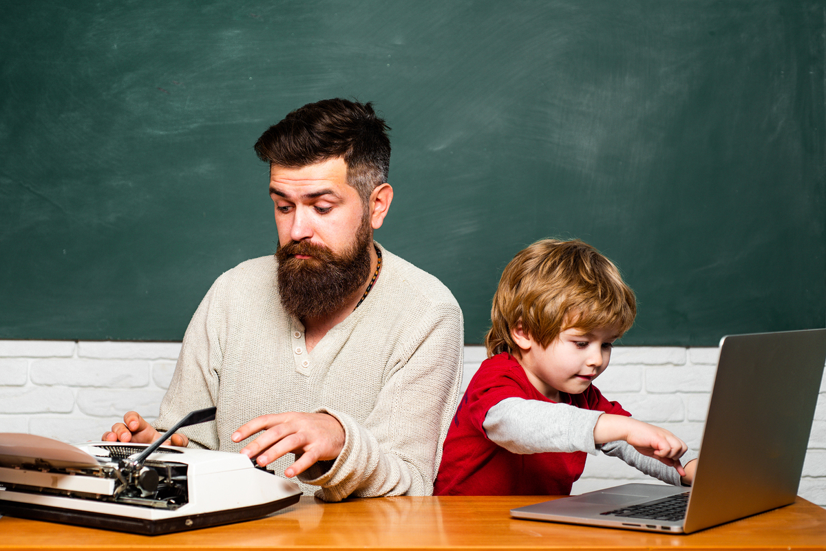 Father typing on an old fashioned typewriter and a son typing on a laptop computer.