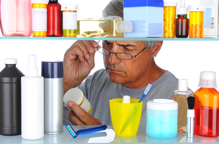 Man looking at a medication label.
