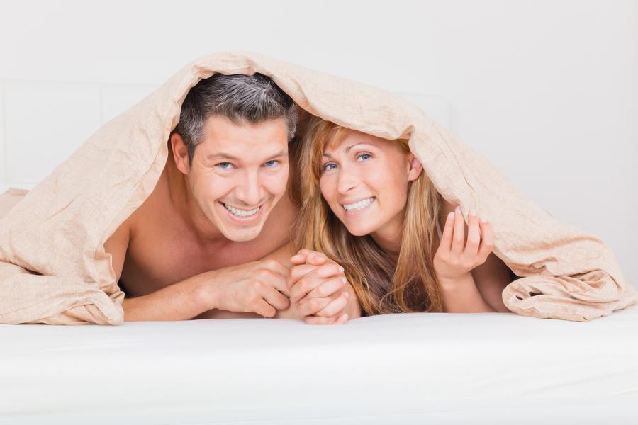Couple hiding under a blanket.