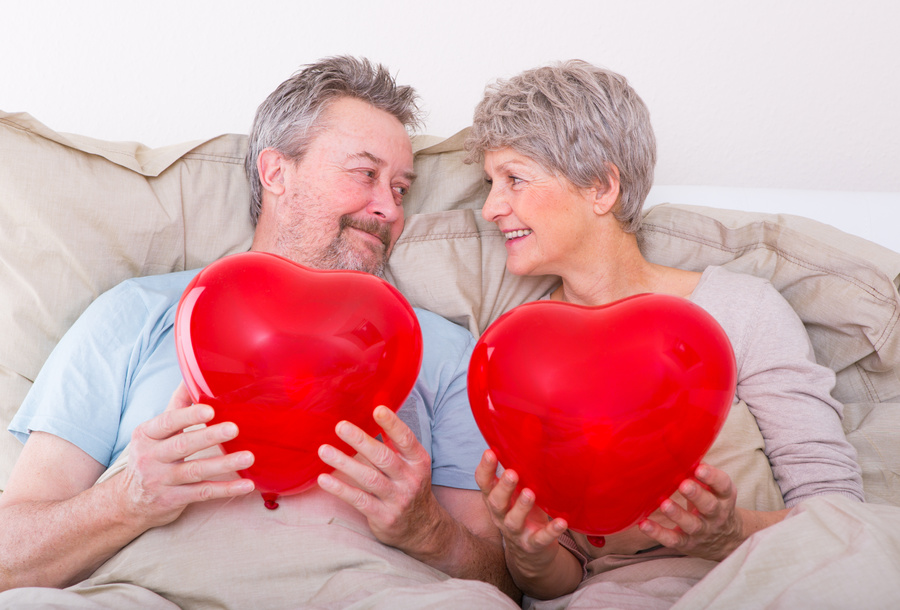 Couple holding red, heart shaped balloons.