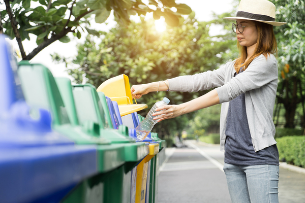 Woman placing a plastic water bottle in a recycle bin.