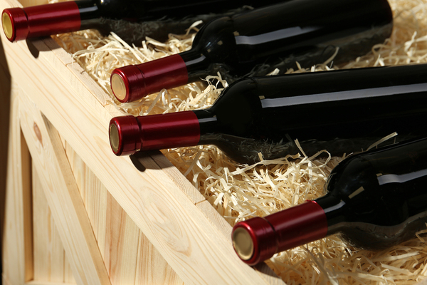 Wine bottles on top of a crate filled with hay.