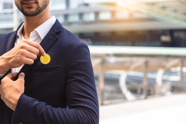 Business man placing a gold coin labeled with a bitcoin symbol in his pocket.