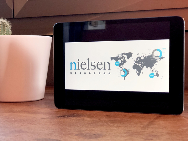 Tablet with Nielsen home page displayed.