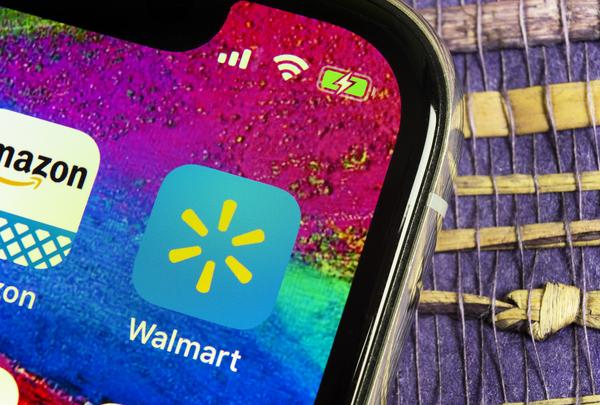 Phone with Walmart and Amazon icons on display.