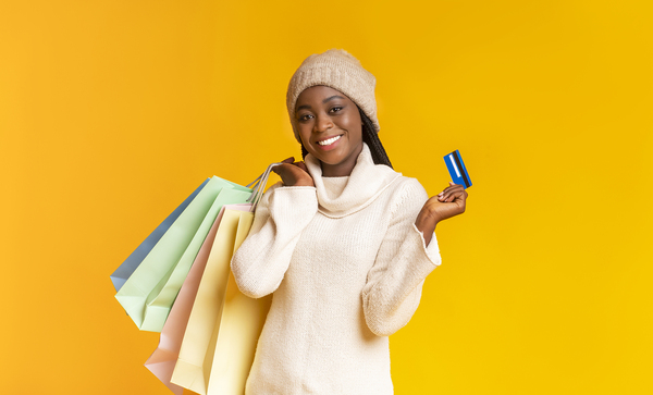 Woman holding shopping bags in one hand and a credit card in the other.