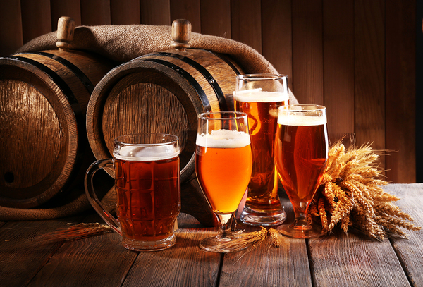 Two wooden barrels and glasses filled with beer.