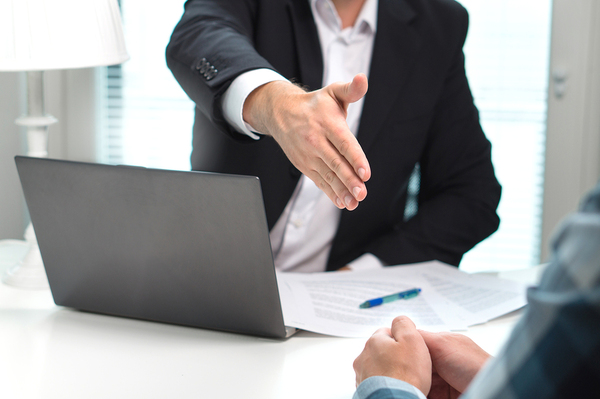 Person reaching out to shake the hand of a potential job candidate.
