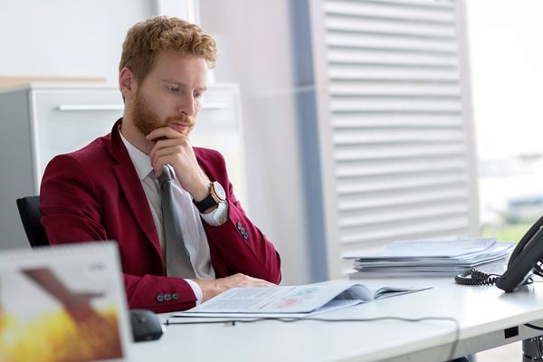 Man sitting at a desk looking at documentation.