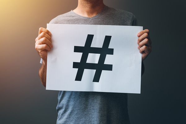 Person holding a post with a hashtag symbol on it.