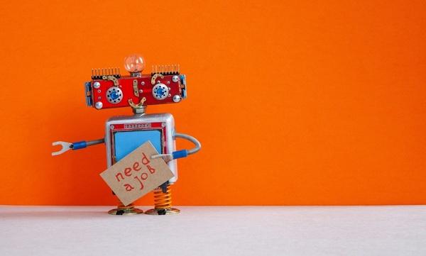 Robot holding need a job sign.