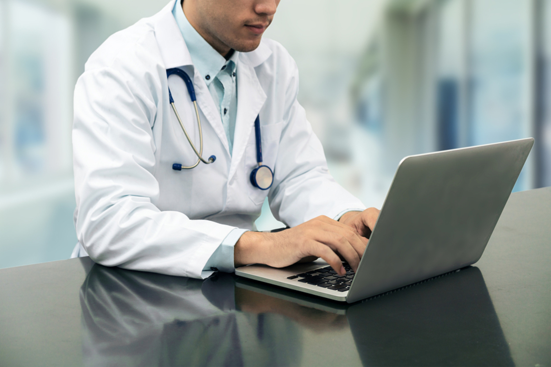 Medical doctor typing on a laptop.