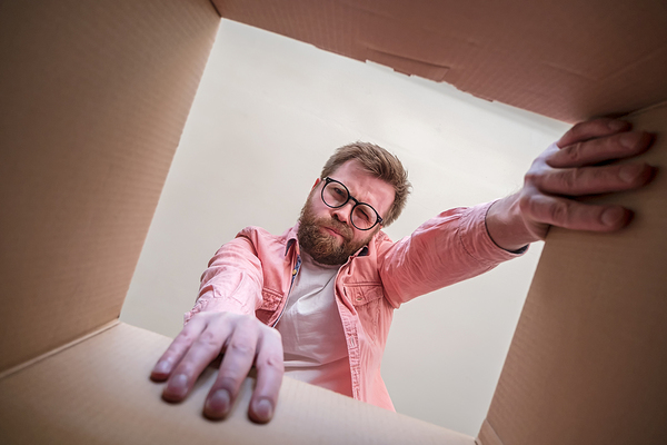 Man looking inside a cardboard box with a puzzled expression.