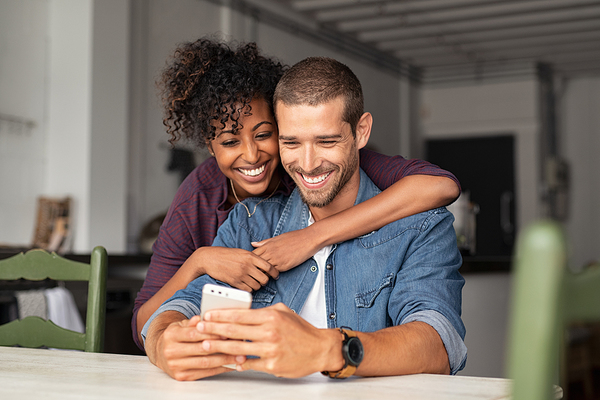 Couple smiling while looking at a phone screen together.
