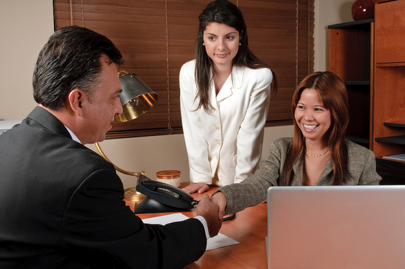 two women sitting across from a man at a desk