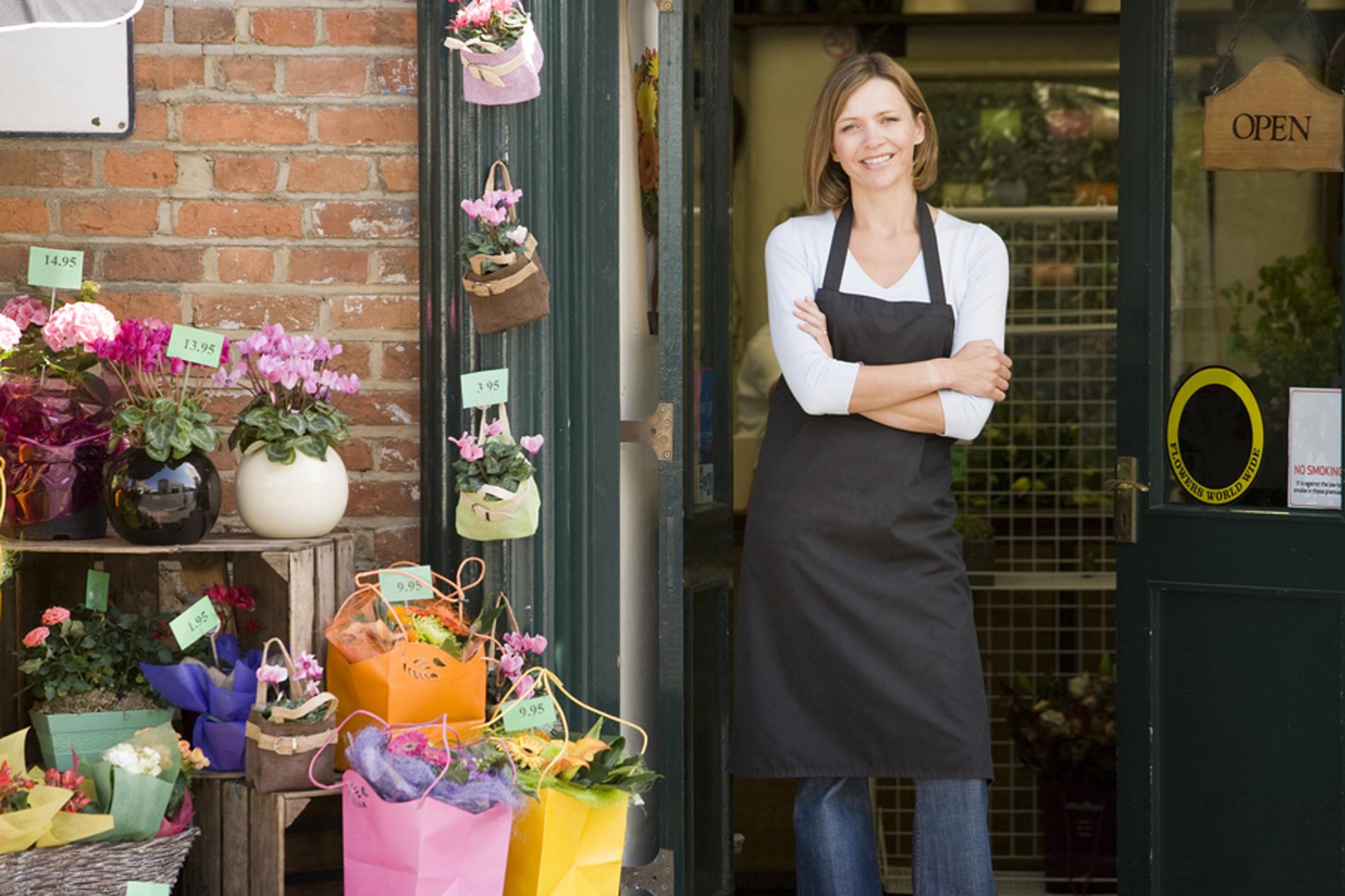 Woman shop owner standing in the entrance doorway.