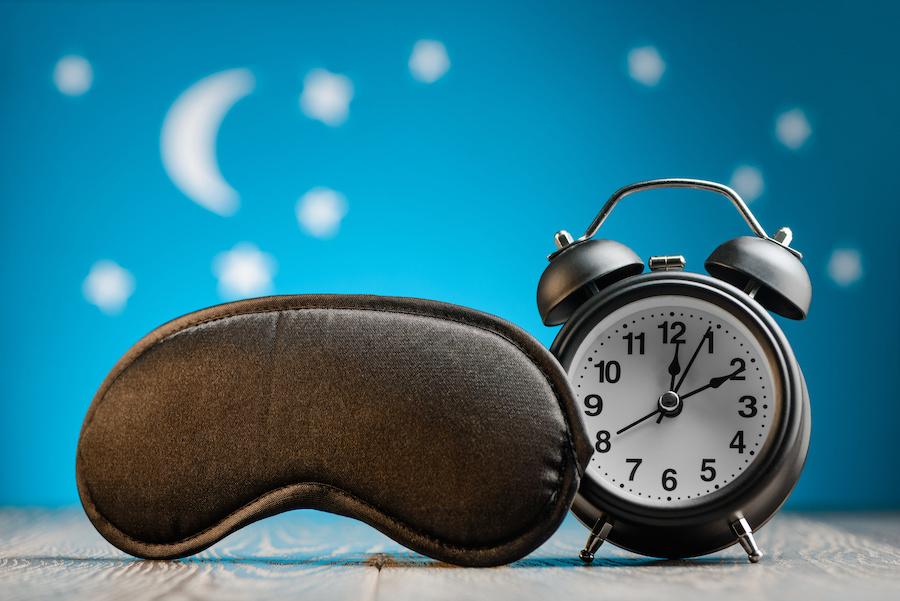 Alarm clock next to an eye mask.