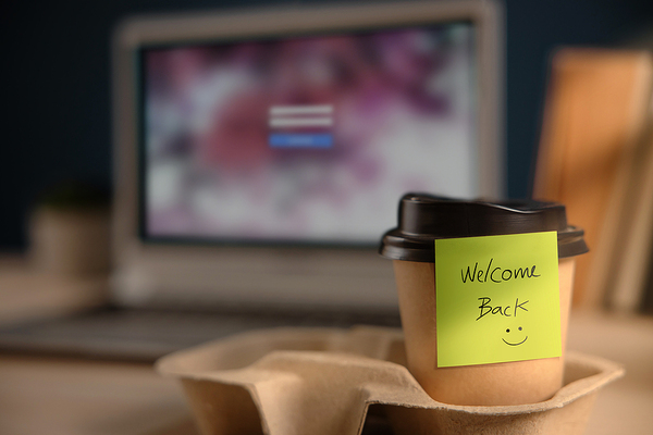 "Coffee cup with a sticky note labeled ""welcome back""."