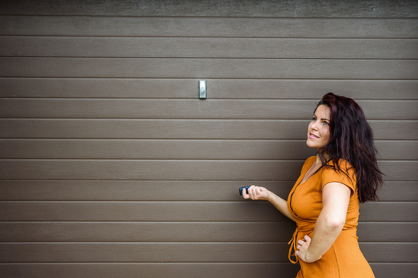 Woman standing next to a garage door with a remote opener.