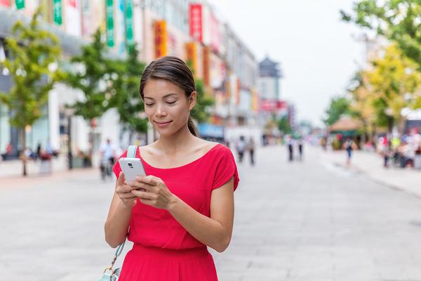 Woman shoppin on phone while walking.