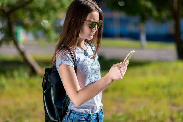 Woman standing outside with a backpack looking at her phone.