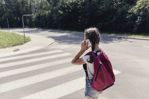 Teenager talking on a phone while walking in a cross walk.